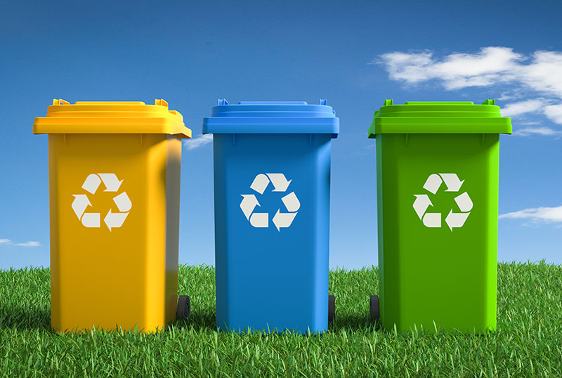 Recycling yellow, blue and green bins on grass